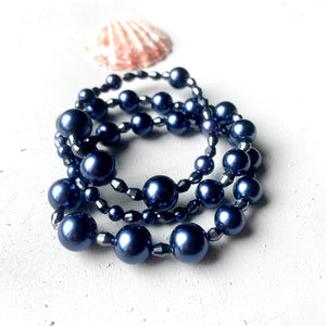 close up side shot navy blue pearl bracelet stack. faceted glass sparkly beads break up the pearls.