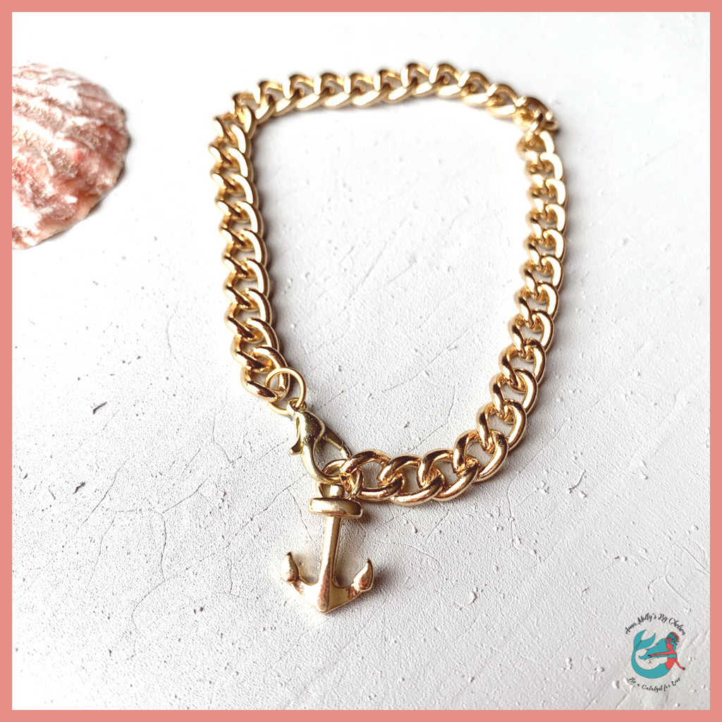 flat lay picture of a bracelet on a desk with seashells. the bracelet is gold chain link with a gold anchor charm