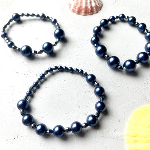 three unique pearl stacking bracelets in a set together. bracelets feature navy blue pearls and faceted glass beads