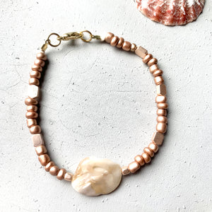 flat lay shot of mother of pearl seashell bracelet with fair trade certified rose gold seed beads