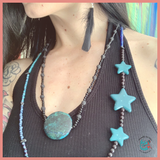 portrait shot of brunette model wearing feather earrings and upcycled beaded jewelry. The layered necklaces shes wearing have teal green river rock beads, lava rock beads, and black seed beads. Shes wearing a black halter top and has some tattoos.