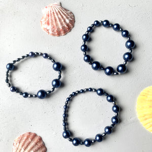 flat lay shot of three bracelet set with seashells. the bracelets are stretchy stacking bracelets with navy blue glass pearls and faceted glass beads
