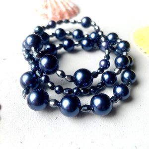 navy blue pearl and faceted glass bead bracelet stack close up shot of three stretchy bracelets stacked together