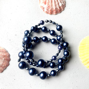 over head shot of three stretchy faux pearl bracelets stacked together. the bracelets are made with elastic cord and faux navy blue pearls and faceted glass beads