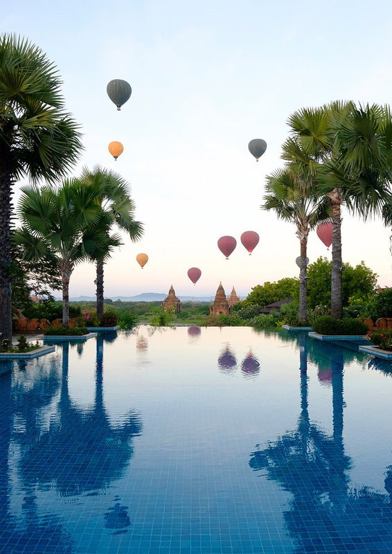 インテリア・フォトパネル「Hot air balloons and palm trees reflecting in swimming pool at Bagan」の画像(amana online storeの額装商品画像)