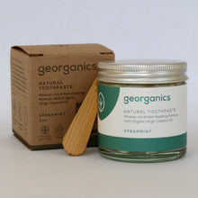 jar of natural toothpaste with bamboo scoop and recyclable cardboard box