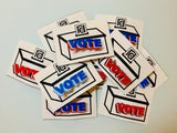 There is a pile of pins on paper--the pins all read VOTE in three colors and are on a card that looks like a ballot box.