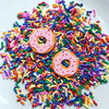 Two earrings on a pile of colorful sprinkles with hypoallergenic hooks and shaped like frosted doughnuts. They are pink and orange with cut outs for sprinkles.