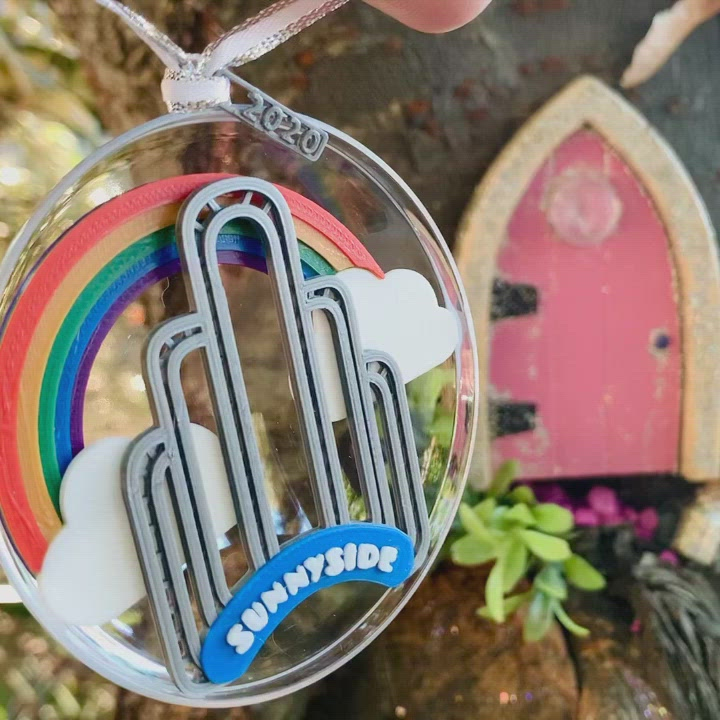 Outside of a pink fairy door in a tree, a hand dangles our limited edition ornament for 2020--It features the art deco arch in Sunnyside, Queens, NYC, with a rainbow and clouds behind it. In the video the ornament is turned, revealing a small fairy door at the bottom of the arch.