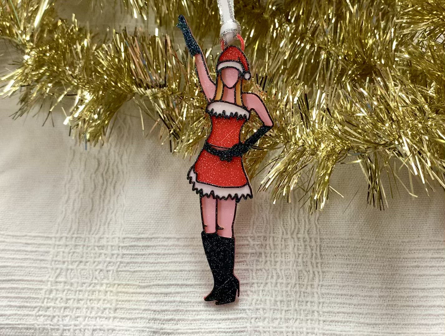 There is a white fabric background with gold garland. Laying on top of these is a 3D printed ornament from R+D. The ornament is printed in a plant based filament. It is shaped like Regina George from the movie Mean Girls. She is striking the iconic pose at the beginning of performing Jingle Bell Rock, wearing black gloves and boots and a red outfit with white trim. The entire ornament is covered in glitter to shimmer and shine in the light.