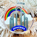 Load image into Gallery viewer, An image of our limited edition ornament for 2020--It features the art deco arch in Sunnyside, Queens, NYC, with a rainbow and clouds behind it. When you flip it over, there is a small fairy door at the borrow of the arch.