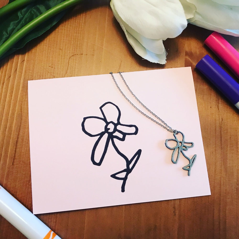 In the middle of the frame is a pink card with a flower drawn on it. Next to the card is a necklace with a 3D printed pendant that is the same as the  drawing.