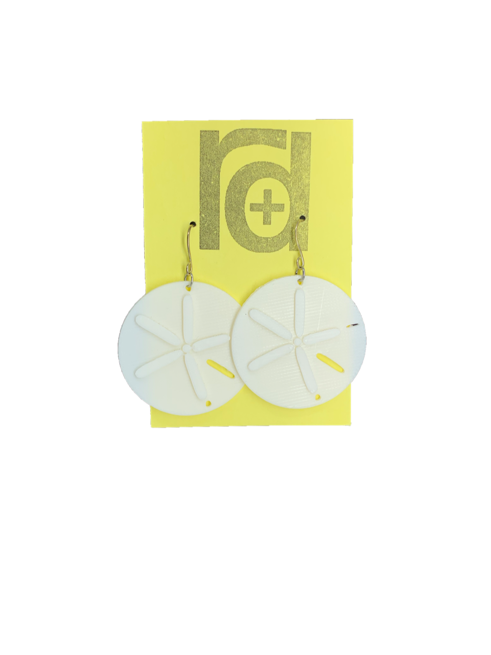 Two white earrings on a yellow earring card. The earrings look like sand dollars with a star burst patten that is raised from he surface.