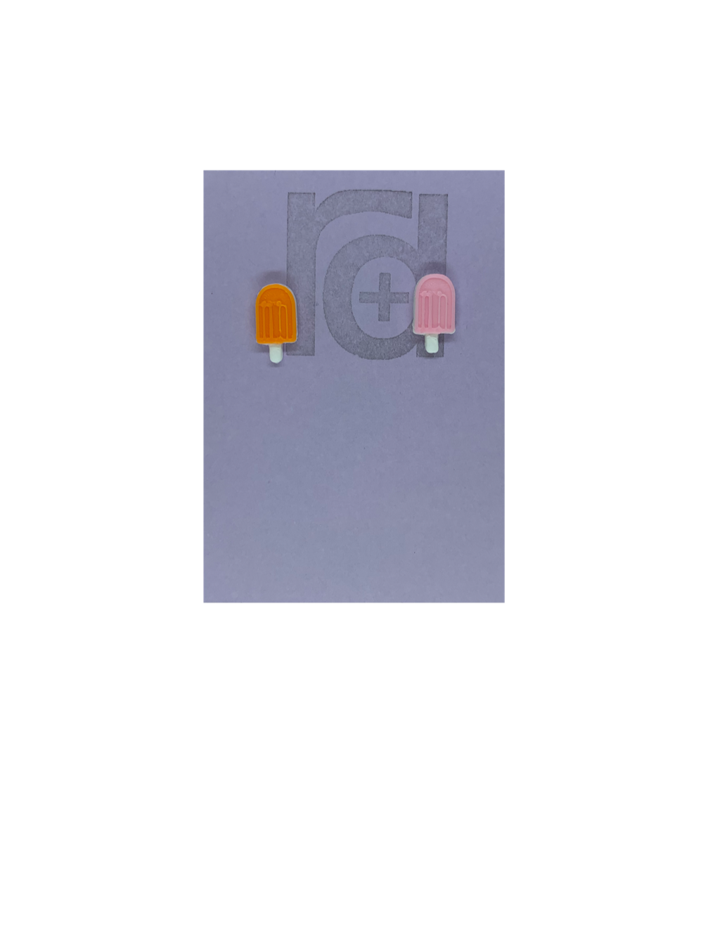 Two small and detailed R+D earrings are shown on a purple earring card. They are shaped as popsicles with white sticks. The earrings are mismatched, one popsicle is a vibrant orange and one is light pink