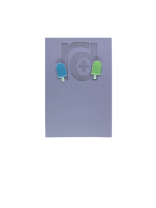Two small and detailed R+D earrings are shown on a purple earring card. They are shaped as popsicles with white sticks. The earrings are mismatched, one popsicle is light blue and one is light mint green.