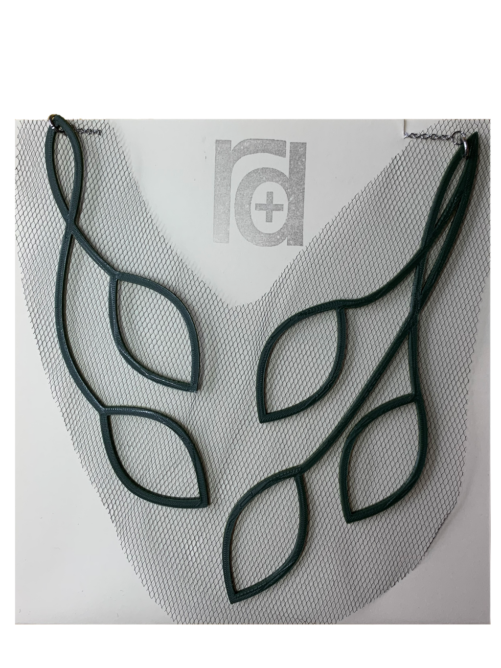 Shown on cream paper packaging, this 3D printed necklace has vines that twist to leaves in a elegant way. They are printed in a sustainable olive green filament with a black tulle fabric embedded.