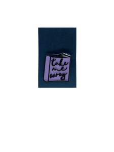 On a dark blue card is a 3D printed pin. It is the shape of a  paper back book. IThe books light purple, with white pages and has details outlined in black. On the cover, it reads, Take me away in a scripted cursive font.