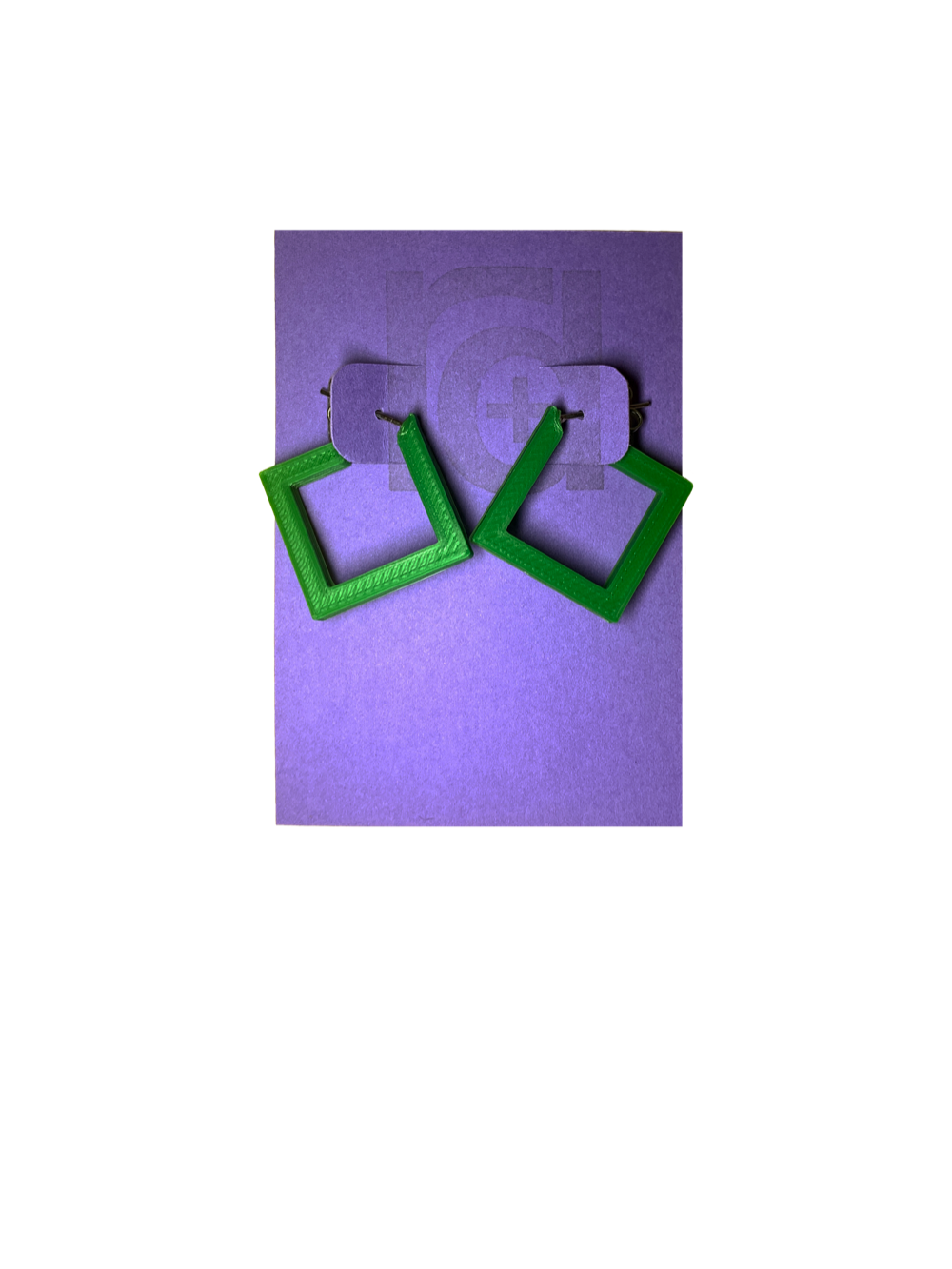 On a bight purple R+D card are two 3D printed earrings. They are hoops that are in the shape of squares. These are printed in a bright kelly green.