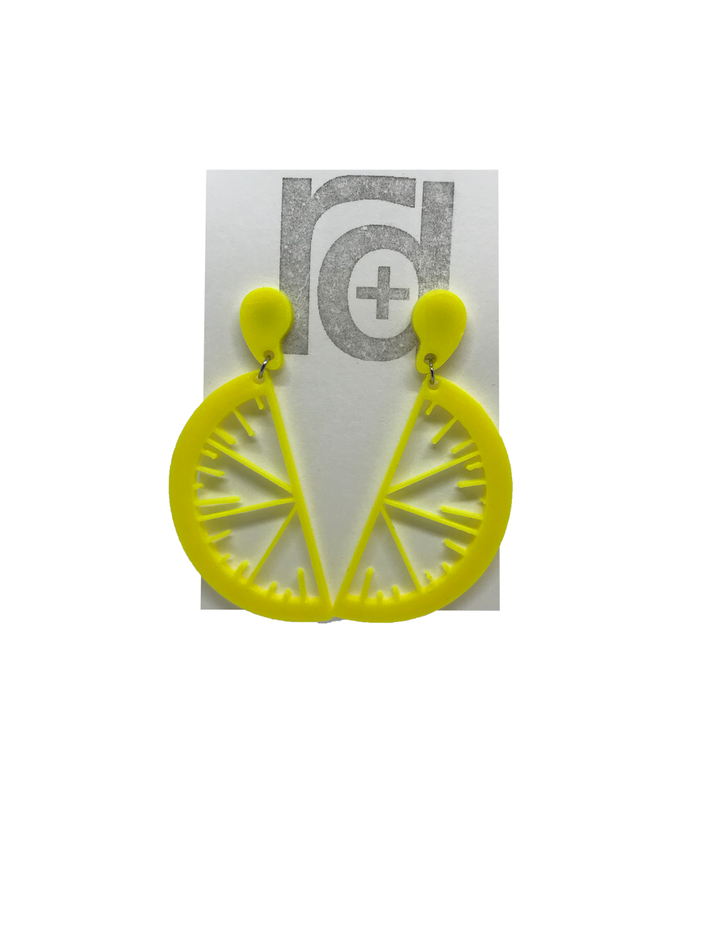 On a white paper earring card are two R+D earrings. They are two slices of fruit hanging from drops of fruit juice. These are yellow like bright lemons.