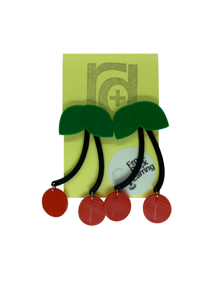 Hanging off of a yellow earring card are two statement earrings  shaped like cherries. They have green leaves that are worn on the front of the ear lobe with two black stems that lead to bright red cherries. The stem is worn behind the ear to give depth to this classic style that will match any picnic or rock a billy outfit.