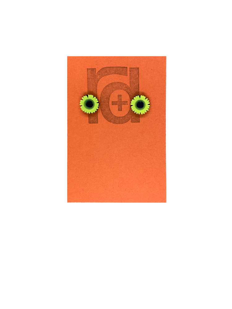 On a orange earring tag are two small and detailed  R+D studs. They are  shaped as sunflowers with black centers and bright yellow petals all around.