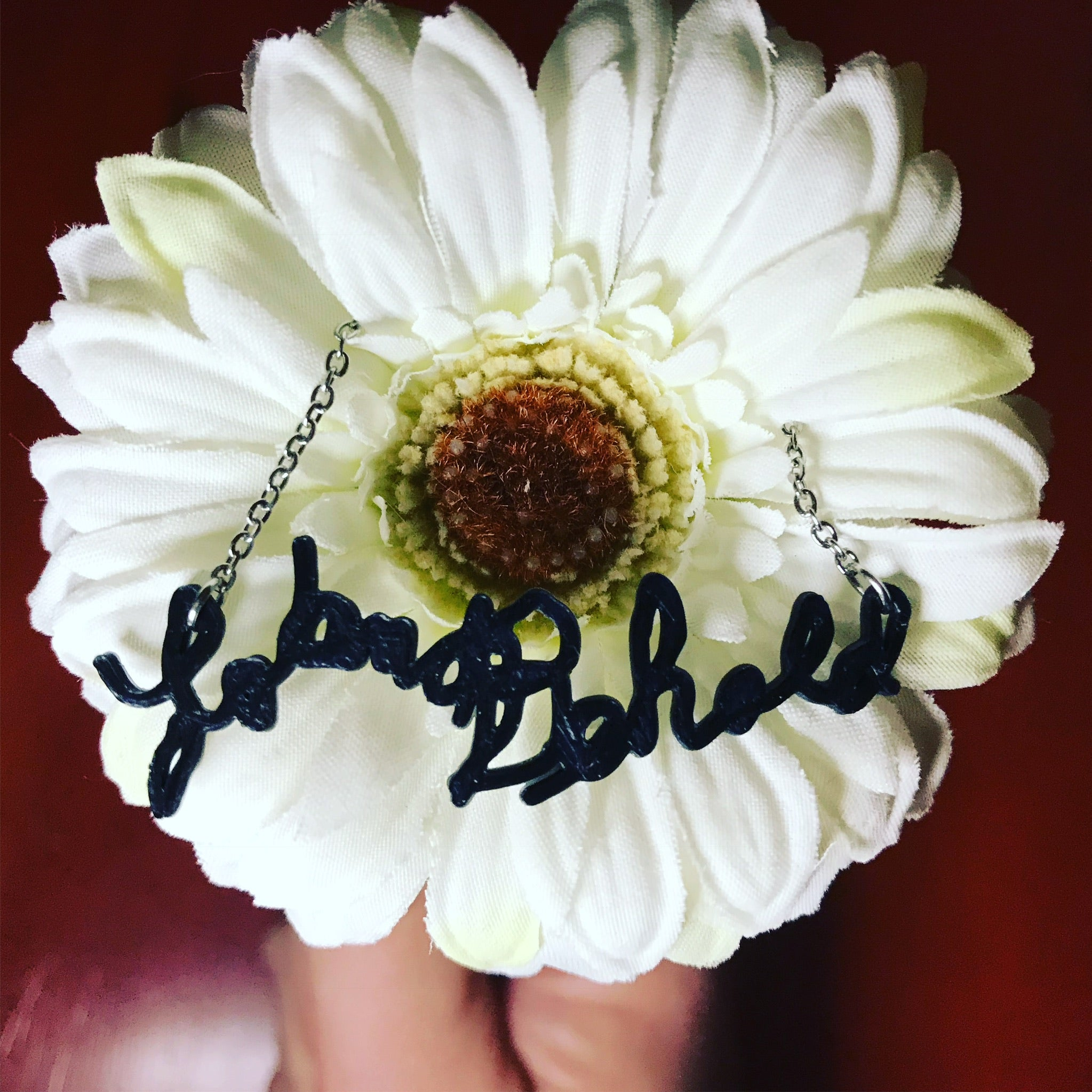 There is a large daisy with a necklace in the middle. The necklace has a 3D printed pendant made from a sample of handwriting.