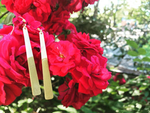 Hanging off of a cluster of bright red roses are two earrings. They are long white dangles that have been dipped in a gold metallic paint.