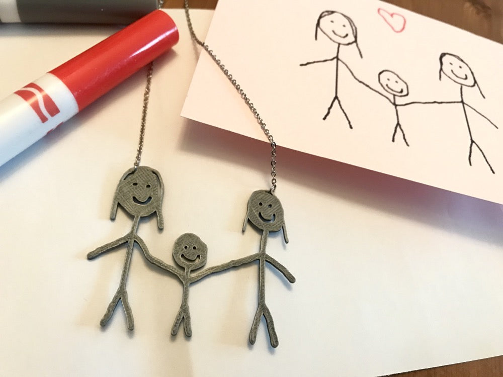 IN the background is a card with a stick figure family drawn on it. In the foreground is a necklace that features a 3D Printed pendant that is made from the drawing on the card.