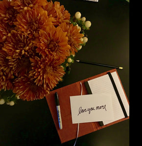 "Shown from above is a notebook with a card that ""love you more"" is written on."