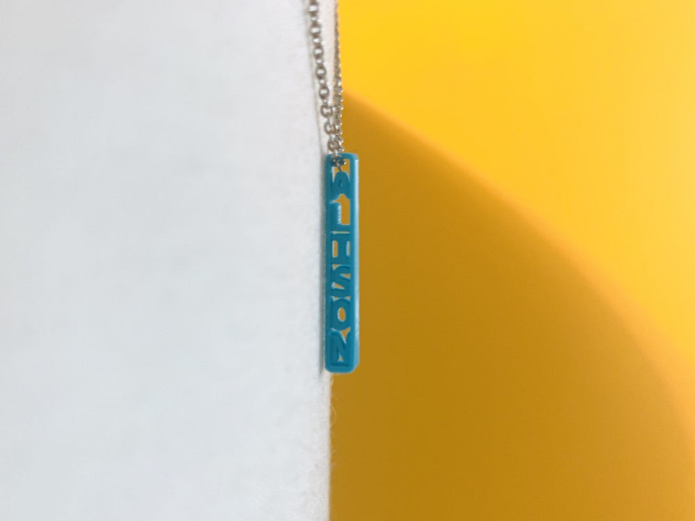Hanging between a white background and a yellow background is a 3D printed pendant. It is a thin and tiny pendant that has the name ALISON printed on it in a bright teal plant based filament.