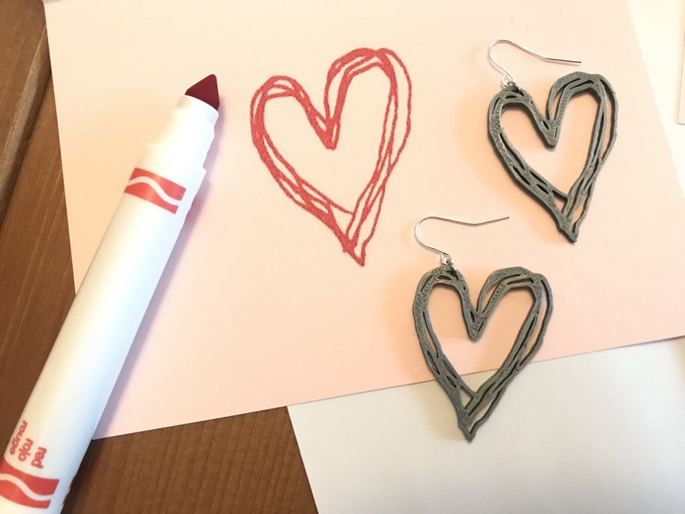 There is a pink card with a uncapped red marker. On the card is a heart drawn with the marker. There are two earrings that are in the same shape as the heart drawing. They are 3D printed with a silver plant based filament.