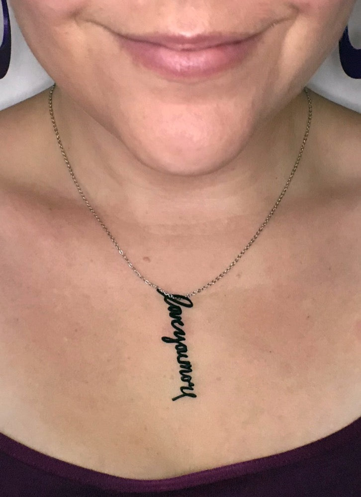 This is a close up of a necklace being worn. There is a 3D printed pendant that has the words, love you more, and is made from a handwriting sample.