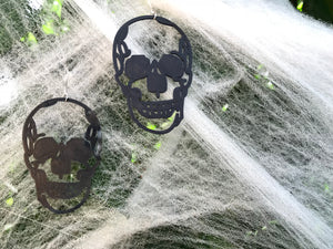 Hanging off of fake cobwebs for Halloween are two large black skull earrings. They are realistic in their shape and could be considered edgy or creepy.