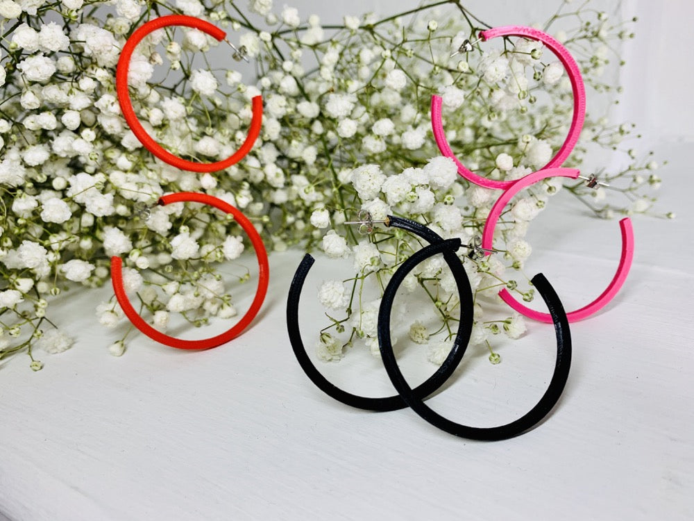On a white background are springs of baby's breath flowers with three pairs of 3D printed hoop earrings hanging off of them. They are lightweight, plant based, and durable. These are shown in a bright red, black, and hot pink.
