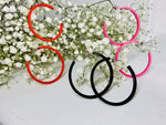 Load image into Gallery viewer, On a white background are springs of baby's breath flowers with three pairs of 3D printed hoop earrings hanging off of them. They are lightweight, plant based, and durable. These are shown in a bright red, black, and hot pink.