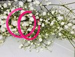 Load image into Gallery viewer, Hanging off of baby's breath flowers are two bright hot pink hoop earrings. These earrings are lightweight (light enough to hang from these delicate branches) and made from a plant based filament.