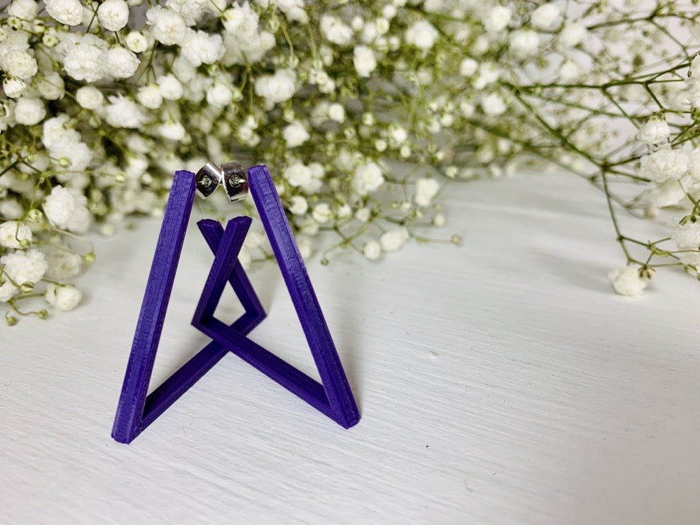 The background is filled with baby's breath flowers. In the foreground there are two 3D printed earrings. They are printed in a plant based purple filament and are shaped as triangle hoops. In the photo they are standing up to create a unique geometric structure.