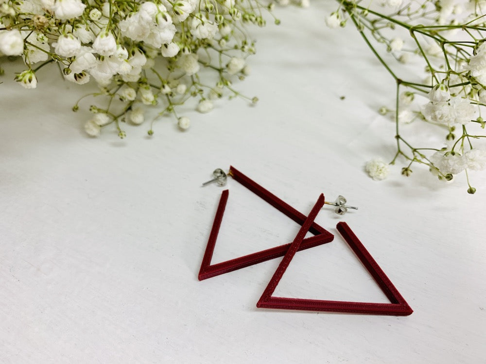 Laying on a white background are two R+D 3D printed earrings. They are triangle hoops that are printed in a plant based filament that is a deep red or merlot color. On the edges of the photo springs of baby's breath flowers are laying down