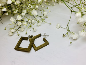 On a white background and surrounded by sprigs of baby's breath flowers are two square hoops that are 3D printed in a gold plant based filament.