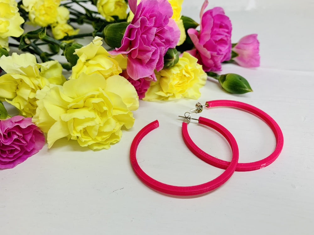 In the background are yellow and pink carnations. Laying in front of them are two hot pink 3D printed hoops.