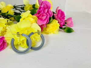 Resting in front of yellow and pink carnations are two 3D printed hoops. They are silver and chunky in their shape.