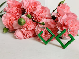 On a white background and surrounded by bright pink carnations are two square hoops that are 3D printed in a kelly green plant based filament.