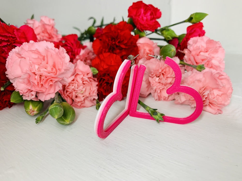 Resting in front of pink and red carnations are two 3D printed hoops from R+D. The hoops are in the shape of hearts with 3 colors layered on top of one another: white, light pink and hot pink.