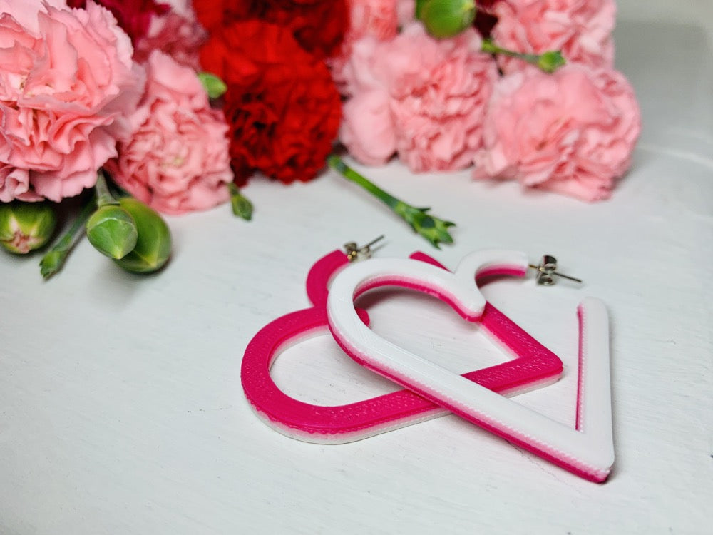Laying on a white background are two 3D printed hoop earrings from R+D. They are layered with three colors: white, light pink, and hot pink. One is flipped over so that the color variations are visible. In the background are bunches of red and pink carnations with green buds reaching out of the cluster.