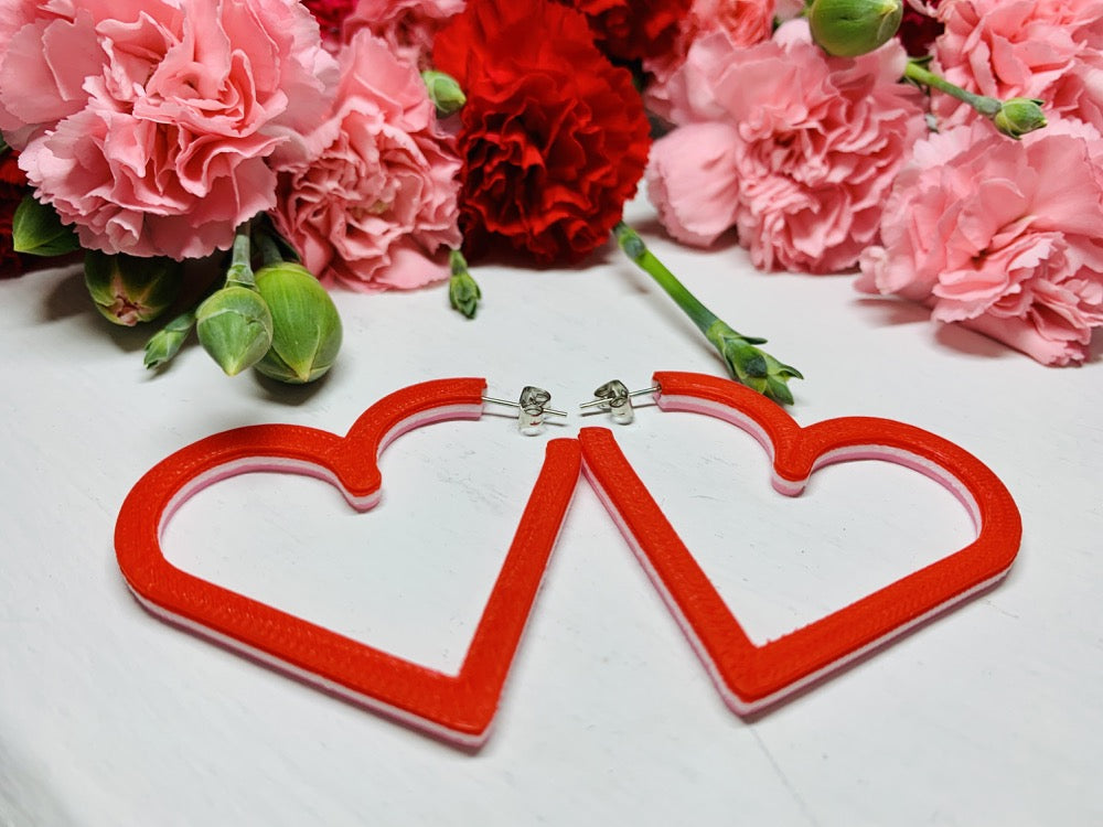 Laying on a white background are two 3D printed hoop earrings from R+D. They are layered with three colors: Light pink, white, and red. In the background are bunches of red and pink carnations with green buds reaching out of the cluster.