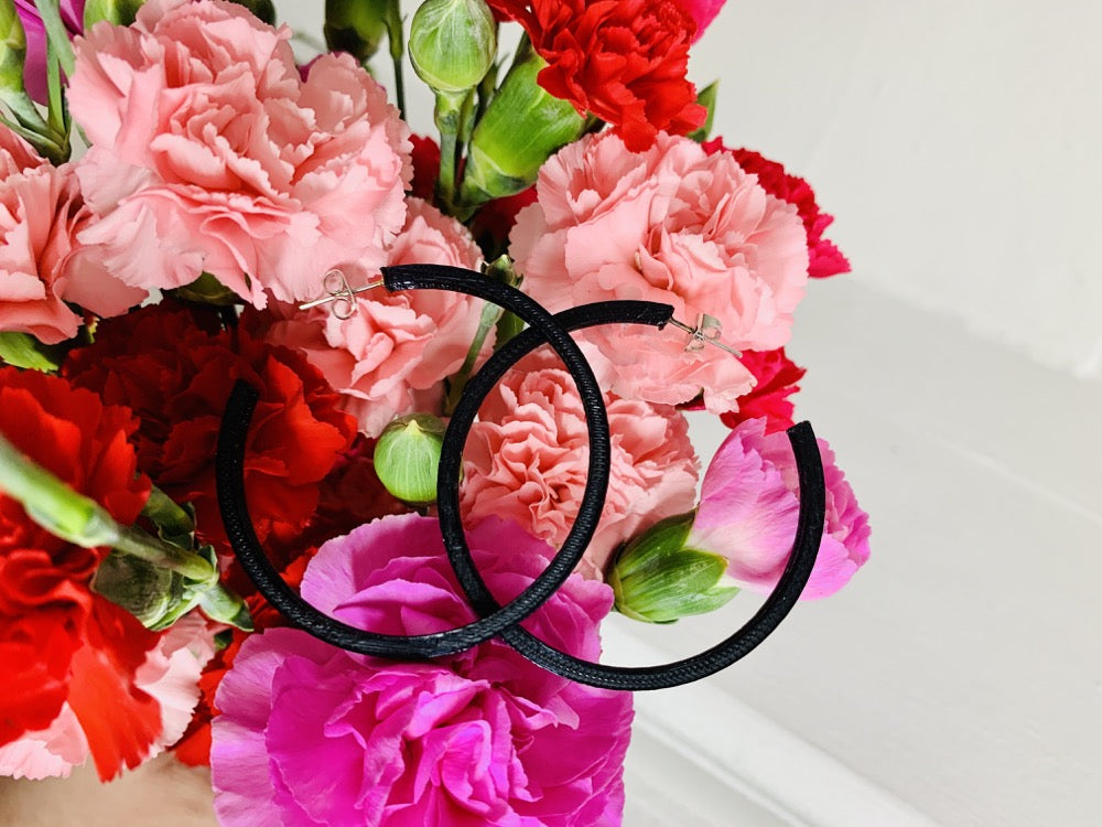 In the background is a bouquet of pink, red, and fuchsia carnations. Resting on the bouquet are two 3D printed hoop earrings. They are black, lightweight, and made from a plant based filament.