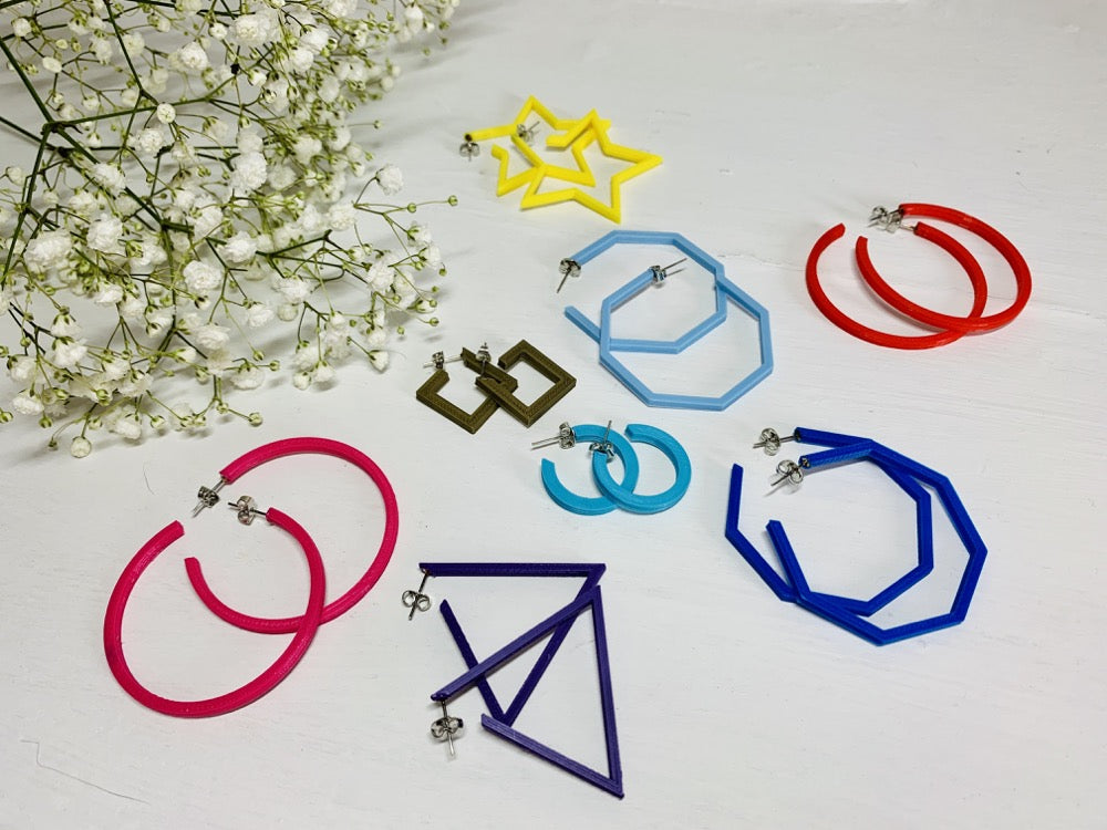 In the upper corner is a sprig of baby's breath. In the foreground there are 8 different pairs of R+D 3D printed hoops. They range in colors from hot pink and red to blues, purple, and gold. They also range in shapes. There are hexagons, smooth hoops, triangles, squares, and stars.