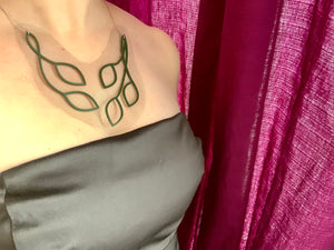 This shows a woman wearing a statement necklace and a satin black strapless dress. The necklace is olive green vines and leaves that twist into an elegant v shape. The piece is 3D Printed with sustainable plant based filament. It is olive green and embedded with a black tulle fabric so that there is a gap between the leaves and it almost has the effect of floating across one's collar bones.
