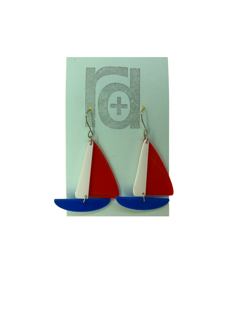 On a light blue earring card are two R+D earrings. They are shaped as sailboats with three pieces: A thin white sail, and larger bright red sail and a classic cobalt blue hull.