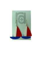 Load image into Gallery viewer, On a light blue earring card are two R+D earrings. They are shaped as sailboats with three pieces: A thin white sail, and larger bright red sail and a classic cobalt blue hull.